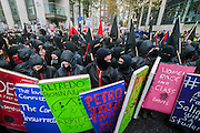 A group of hooded students with anarchist flags carry placard shields and hold smoke flares - A student march against fees and many other issues starts in Malet Street and heads for Westminster via the West End.