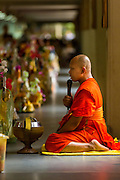"12 JULY 2014 - PHRA PHUTTHABAT, SARABURI, THAILAND: A monk leads a chanting service before the Tak Bat Dok Mai at Wat Phra Phutthabat in Saraburi province of Thailand. Wat Phra Phutthabat is famous for the way it marks the beginning of Vassa, the three-month annual retreat observed by Theravada monks and nuns. The temple is highly revered in Thailand because it houses a footstep of the Buddha. On the first day of Vassa (or Buddhist Lent) people come to the temple to ""make merit"" and present the monks there with dancing lady ginger flowers, which only bloom in the weeks leading up Vassa. They also present monks with candles and wash their feet. During Vassa, monks and nuns remain inside monasteries and temple grounds, devoting their time to intensive meditation and study. Laypeople support the monks by bringing food, candles and other offerings to temples. Laypeople also often observe Vassa by giving up something, such as smoking or eating meat. For this reason, westerners sometimes call Vassa ""Buddhist Lent.""<br />     PHOTO BY JACK KURTZ"
