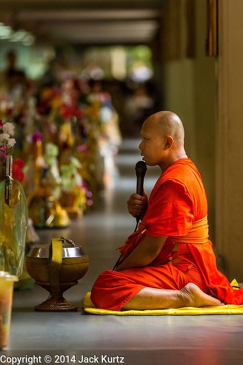 12 JULY 2014 - PHRA PHUTTHABAT, SARABURI, THAILAND: A monk leads a chanting service before the Tak Bat Dok Mai at Wat Phra Phutthabat in Saraburi province of Thailand. Wat Phra Phutthabat is famous for the way it marks the beginning of Vassa, the three-month annual retreat observed by Theravada monks and nuns. The temple is highly revered in Thailand because it houses a footstep of the Buddha. On the first day of Vassa (or Buddhist Lent) people come to the temple to &quot;make merit&quot; and present the monks there with dancing lady ginger flowers, which only bloom in the weeks leading up Vassa. They also present monks with candles and wash their feet. During Vassa, monks and nuns remain inside monasteries and temple grounds, devoting their time to intensive meditation and study. Laypeople support the monks by bringing food, candles and other offerings to temples. Laypeople also often observe Vassa by giving up something, such as smoking or eating meat. For this reason, westerners sometimes call Vassa &quot;Buddhist Lent.&quot;<br />     PHOTO BY JACK KURTZ