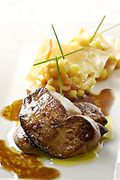 Two slices of foie gras, sauteed, port reduction sauce, on a white plate, phillo squares and corn on back