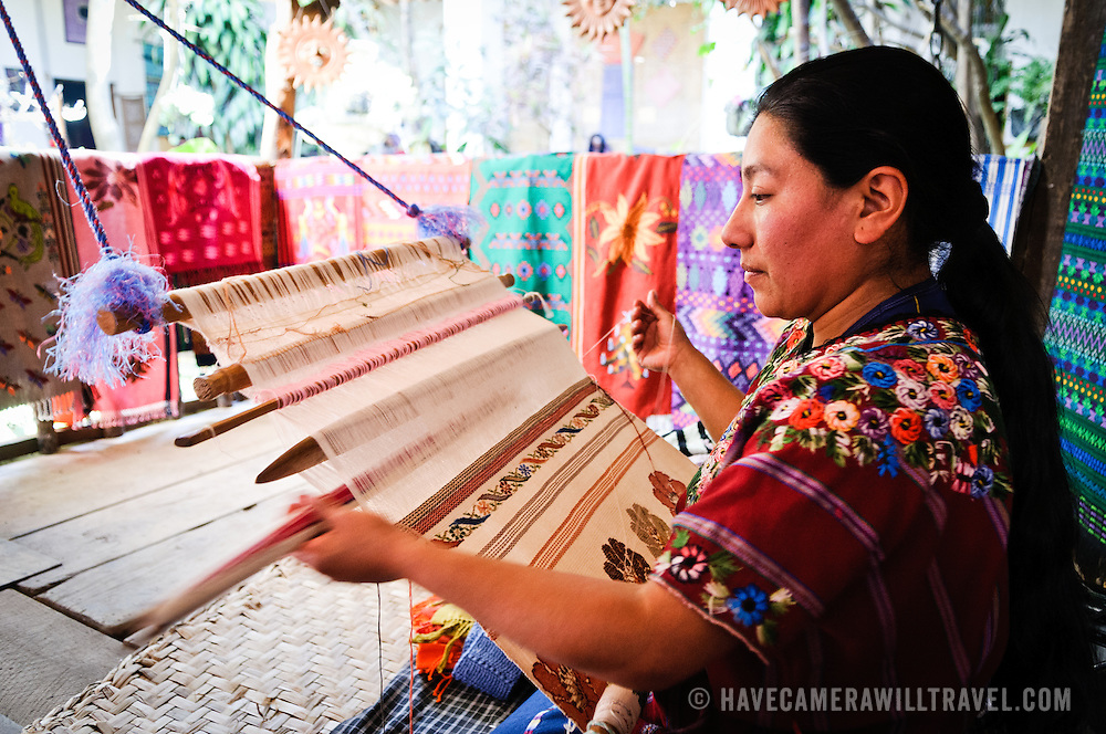 Woman using a traditional loom at Casa del Tejido Antiguo, an indigenous textile museum and market in Antigua, Guatemala