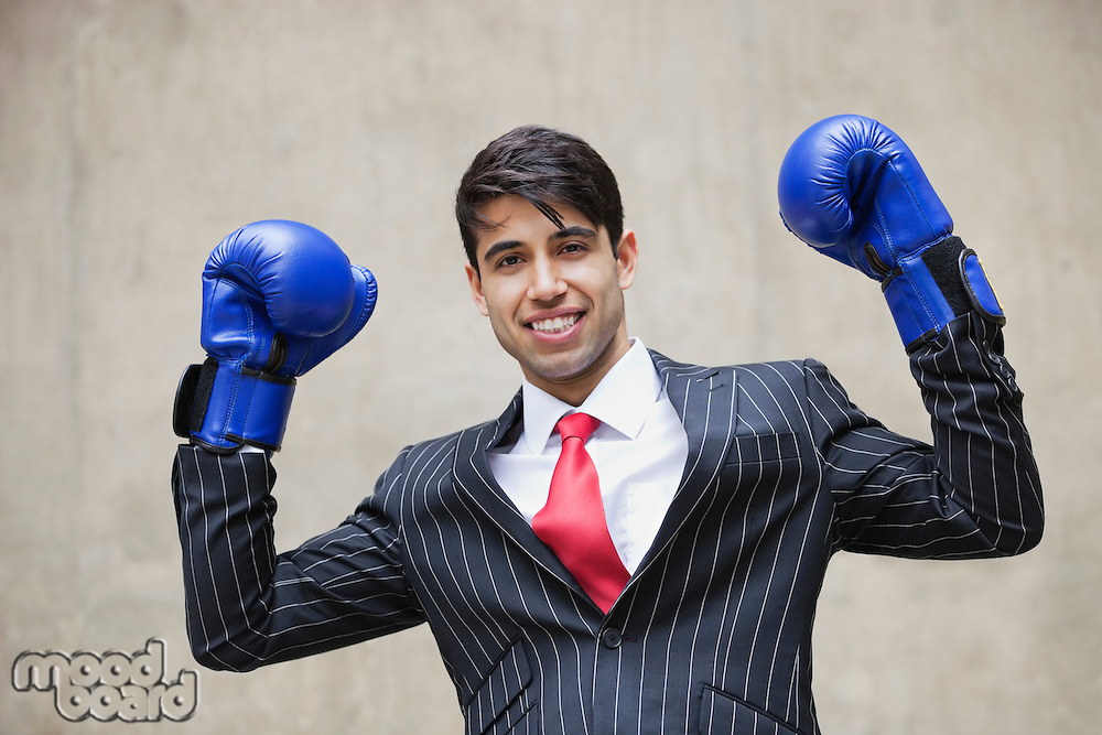 Portrait of an Indian businessman celebrating victory while wearing blue boxing gloves against gray background