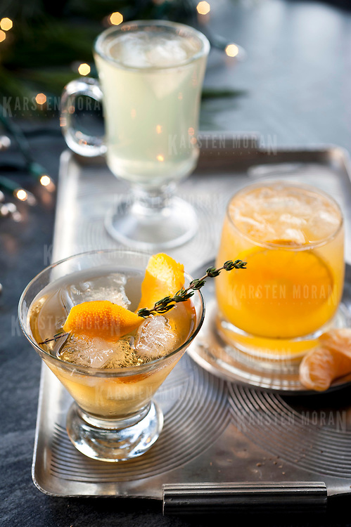 """December 2, 2013 - New York, NY : A selection of holiday cocktails, prepared and styled by Suzanne Lenzer, include, from front to back, the """"Tabard Cocktail"""" (with sprig of Thyme), the """"Bad Day at Work"""" (garnished with clementines), and the """"Green Tea Punch"""" (dusted with grated nutmeg). CREDIT: Karsten Moran for The New York Times"""