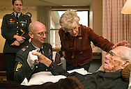 "Retired Air Force Capt. Gerald D. Binks lies in bed at St. John's Living Center with his wife Mary Lynn Yose Binks and American Legion Post 43 Commander David Bentlage at his side. The 87–year–old World War II veteran piloted B-17 bombers over Germany and was shot down and captured in 1944. Capt. Binks, originally from Casper, Wyo. suffers from congestive heart failure. ""It's time for me to go off to the happy hunting ground,"" Binks said."