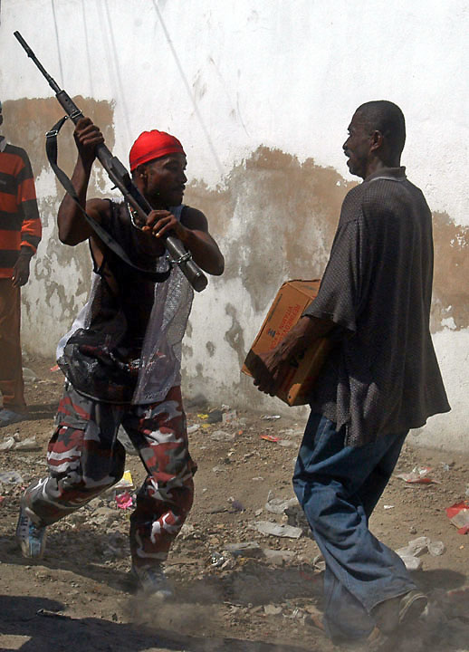 A paramilitary stops a looter outside a food distribution center in Gonaives, Haiti, February 20, 2004. food distribution led to looting when paramilitaries stormed the building. (Photo by William B. Plowman)