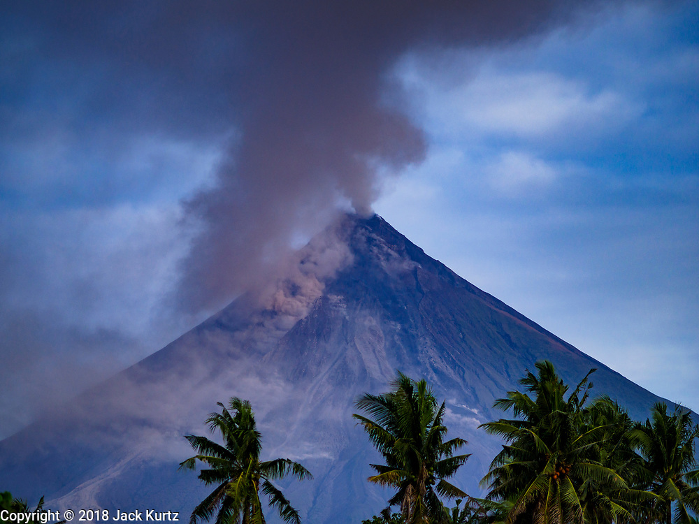 30 JANUARY 2018 - LEGAZPI, ALBAY, PHILIPPINES: The Mayon volcano, as seen from Legazpi, sends a cloud of ash into the sky. Mayon volcano continued to erupt but not as dramatically as it did last week. The small eruptions are still sending ash clouds over communities west of the volcano and the government is encouraging people to stay indoors, wear face masks and avoid strenuous activities when ash is falling.     PHOTO BY JACK KURTZ