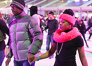 At Bryant Park's ice skating rink that night, the colorful rink is filled with people skating and talking with friends. Manhattan, New York, USA. November 9, 2013.