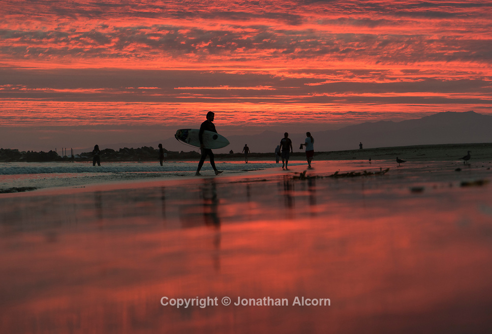 A surfer walks in during a brilliant dusk sky in Venice