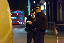 © Licensed to London News Pictures. 26/10/2016. LONDON, UK.  Police officers at the police cordon around East Street in Barking, east London. Police were called at 18:12 on Wednesday 26th October. Officers and the London Ambulance Service attended the scene and found a man in his late 20s with stab wounds to the abdomen. He was taken to an east London hospital where he remains with life threatening injuries.  Photo credit: Vickie Flores/LNP
