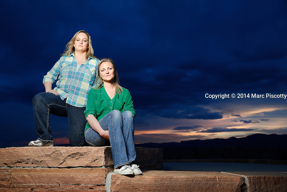 SHOT 4/18/14 7:34:04 PM - Former Columbine High School students Jennifer Hammer (left), 33, of Commerce City, Co. and Heather Egeland, 32, of Littleton, Co. pose for a portrait at the Columbine Memorial recently. The two are co-founders of The Rebels Project, a support group that has helped survivors of other mass shootings around the country, from Virginia Tech to Chardon, Ohio to Newtown, Conn. On the day of the Columbine shootings in 1999 the two were huddled in the choir office with about 60 other students hiding from the shooters. They are standing atop Rebel Hill right next to Coumbine High School. (Photo by Marc Piscotty / © 2014)