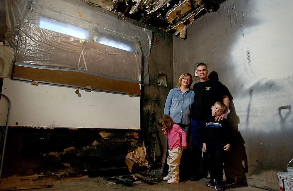 The Larson family, standing in their Council Bluffs, Iowa  home,   utilized U.S. Air Force Temporary Living Facilities at Offutt Air Force Base, Nebraska when the children's bedroom suffered an electrical fire.  The family is safe and well, but will continue to be challenged by the repercussions of this event.  Seen here on 1 March, are (l-r) Raelyn (3), looking at a burn hole in the floor, Liz, U.S. Army Staff Sgt. Scott Larson, and son Taylor.  (5).  Sgt Larson was deployed to Lashkargah, Afghanistan when the 11 Feb fire took place.  Sgt. Larson's unit, Delta Co., 1-168 Infantry of the Iowa National Guard, sent him home on emergency leave, 20 Feb. but will soon be returning as soon to continue his work as the Operations Center NCOIC of the Provincial Reconstruction Team.  (U.S. Air Force photo by Master Sgt. Lance Cheung)