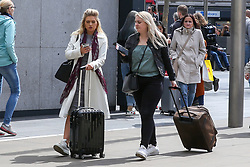 © Licensed to London News Pictures. 04/05/2019. London, UK. Two women arrives at Kings Cross rail station with suitcases, travelling for the May Bank holiday weekend. According to the Met Office many parts of the UK will have snow, hail and thunder for the weekend and the temperature for the May Bank holiday could drop to as low as -6 degrees celsius. Photo credit: Dinendra Haria/LNP