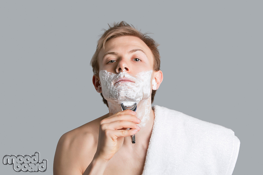 Portrait of young man grooming himself over colored background