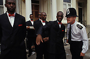 The Nation of Islam talking to a policeman. Notting Hill Carnival, London, UK 1994