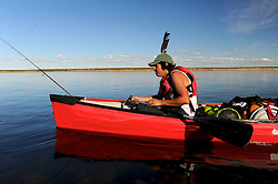 """Miles Catholoque, 14, fishes on his canoe along the Thelon, the largest and most remote game sanctuary in North America, which almost no one has heard of.  For the Akaitcho Dene, the Upper Thelon River is """"the place where God began.""""  Sparsely populated, today few make it into the Thelon. Distances are simply too far, modern vehicles too expensive and unreliable. For the Dene youth, faced with the pressures of a western world, the ties that bind the people and their way of life to the land are even more tenuous. Every impending mine, road, and dam construction threatens to sever these connections. In July and August, 2011 a group of youth paddled to their ancestral hunting ground and spiritual abode.  this next generation of young leaders will be the ones who will need to speak for the Thelon the loudest. (Photo by Ami Vitale)"""