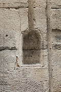 Niche for an oil lantern, carved in a stone wall between 8 and 10 Rue des Grands-Augustins, in the 6th arrondissement of Paris, France. The niche is bottle shaped and has a groove extended upwards where the lamp was hung. Originally the niche would have had a cast iron lockable door. The lamplighter came twice a day - in early afternoon to maintain the lamp and lantern windows, and at dusk to light the lamp. Picture by Manuel Cohen
