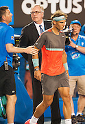 Stanislaus Wawrinka of Switzerland defeated the number one player in the world R. Nadal of Spain (shown here headig to an off court medical time out) to claim the 2014 Australian Open Men's Singles Championship. The Swiss won 6-3 6-2 3-6 6-3 in a match that will be remembered for a confusing and sometimes bizarre final three sets, with Nadal clearly hampered by a left lower back injury and seemingly on the verge of retirement in the second set.. The match was held on center court at Melbourne's Rod Laver Arena.
