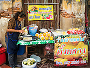07 JUNE 2016 - BANGKOK, THAILAND: A sidewalk fruit seller cuts up fresh pineapple in front of a shuttered shop in Verng Nakorn Kasem, also known as the Thieves' Market. Verng Nakorn Kasem was one of Bangkok's most famous shopping districts. It is located on the north edge of Bangkok's Chinatown, it grew into Bangkok's district for buying and selling musical instruments. The family that owned the land recently sold it and the new owners want to redevelop the famous area and turn it into a shopping mall. The new owners have started evicting existing lease holders and many of the shops have closed. The remaining shops expect to be evicted by the end of 2016.   Bangkok's Chinatown, considered by some to be one of the best preserved Chinatown districts in the world, is changing. Many of the old shophouses are being demolished and replaced by malls and condominium developments.        PHOTO BY JACK KURTZ