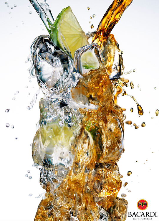 Bacardi and Coke pouring over ice and lime Ray Massey is an established, award winning, UK professional  photographer, shooting creative advertising and editorial images from his stunning studio in a converted church in Camden Town, London NW1. Ray Massey specialises in drinks and liquids, still life and hands, product, gymnastics, special effects (sfx) and location photography. He is particularly known for dynamic high speed action shots of pours, bubbles, splashes and explosions in beers, champagnes, sodas, cocktails and beverages of all descriptions, as well as perfumes, paint, ink, water – even ice! Ray Massey works throughout the world with advertising agencies, designers, design groups, PR companies and directly with clients. He regularly manages the entire creative process, including post-production composition, manipulation and retouching, working with his team of retouchers to produce final images ready for publication.