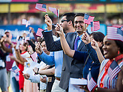 04 JULY 2019  - DES MOINES, IOWA: Just naturalized American citizens wave their American flags after taking the Oath of Citizenship before the Iowa Cubs game. Thirty people became US citizens during a naturalization ceremony at the Iowa Cubs game in Des Moines. The naturalization ceremony is an Iowa Cubs 4th of July tradition. This is the 11th year they've held the ceremony.         PHOTO BY JACK KURTZ