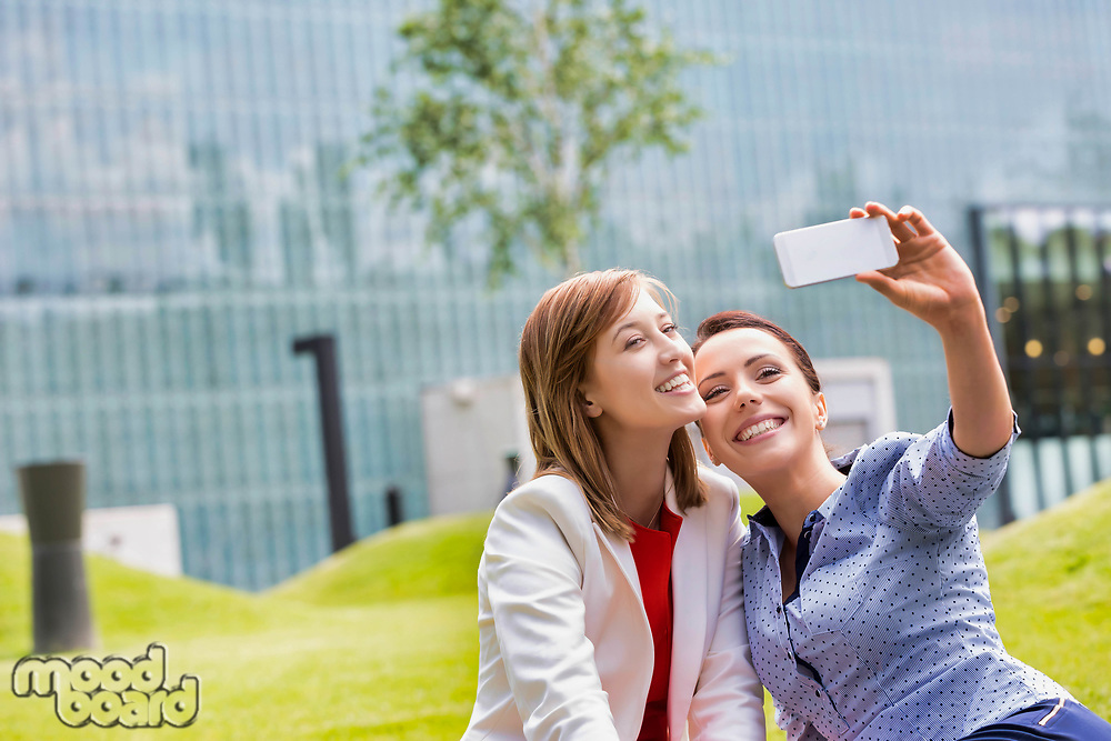 Businesswomen taking selfie while sitting on the grass in park