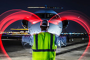 Using high visibility red wands, a lineman simulates waving an aircraft into parking position at night.  Created by aviation photographer John Slemp of Aerographs Aviation Photography. Clients include Goodyear Aviation Tires, Phillips 66 Aviation Fuels, Smithsonian Air & Space magazine, and The Lindbergh Foundation.  Specialising in high end commercial aviation photography and the supply of aviation stock photography for commercial and marketing use.