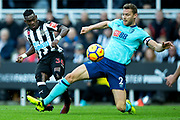 Christian Atsu (#30) of Newcastle United squeezes a shot around the outstretched leg of Simon Francis (#2) of AFC Bournemouth during the Premier League match between Newcastle United and Bournemouth at St. James's Park, Newcastle, England on 4 November 2017. Photo by Craig Doyle.