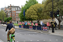 Remain Brexit protesters outside Parliament, London UK 29 April 2019. In the foreground, a man riding a Lime-E electric assist hire bike