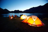 Evening camp on lake in New Zealand with glowing tents and campfire lighting the picture. Two couples sit around the campfire