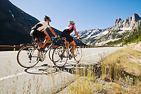 A young couple riding their bicycles up Washington Pass in the North cascades of Washington State, USA.