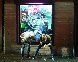"""© Licensed to London News Pictures . 23/12/2017. Manchester, UK. A man checks on the welfare of another , who gives two thumbs up as he sits in the window of a takeaway on Bootle Street , leaning over a pool of vomit between his feet . Revellers out in Manchester City Centre overnight during """" Mad Friday """" , named for being one of the busiest nights of the year for the emergency services in the UK . Photo credit: Joel Goodman/LNP"""