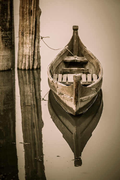 Traditional fishing boat moored to a post under the U Bein Bridge, a crossing that spans the Taungthaman Lake near Amarapura in Myanmar. The 1.2-kilometre bridge was built around 1850 and is believed to be the oldest and longest teakwood bridge in the world.