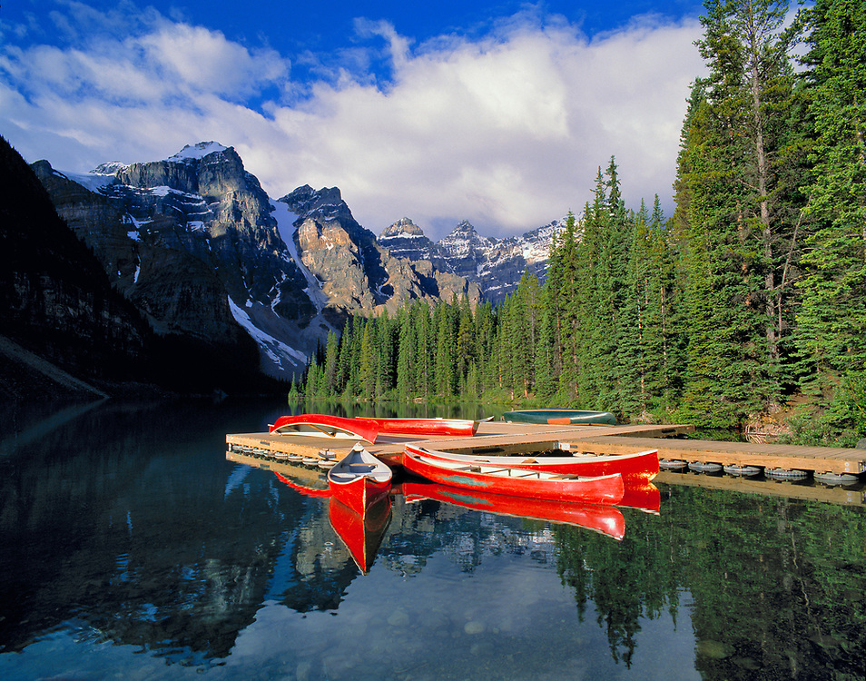 The glassy surface of Moraine Lake mirrors these red canoes in Valley of the Ten Peaks, Banff National Park, Alberta, Canada. ©Ric Ergenbright