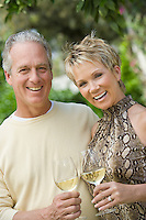 Couple holding wine outdoors, portrait