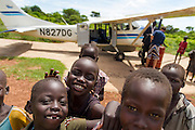 Children crowd near the landing strip in Akot, South Sudan. The small village has a grass runway and is used frequently by AIM Air pilot to refuel.