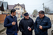 Roma activists Marius Tudor (left) and Marian Daragiuin (right) discussing with a campaigner during the last door to door meeting with Roma community members of Marginenii de Jos before the final round of the presidential elections two days later in Romania. The campaigners supported Victor Ponta who lost the presidential elections in the end.