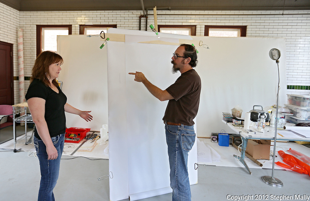 Tom Torluemke (from right) talks with Jodee Staebler of Robins before starting a sketch of her at the Firehouse Studio next to CSPS Hall, 1103 Third St SE in Cedar Rapids on Saturday afternoon, June 2, 2012. In the background is the canvas that Torluemke will use for the final painting. (Stephen Mally/Freelance)