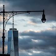 Dramatic sky and clouds formations with old fashion light pole on 7th Avenue South in foreground and One World Trade Center in background.<br /> <br /> 1 WTC; the current building was dubbed the &quot;Freedom Tower&quot;.