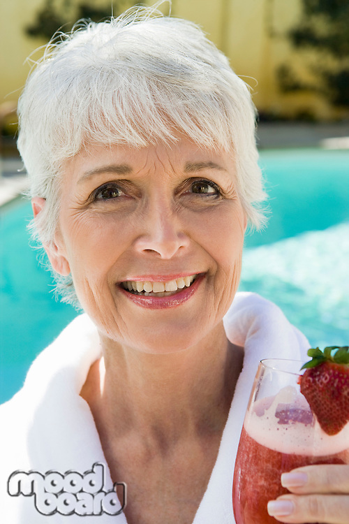 Portrait of senior woman holding strawberry cocktail