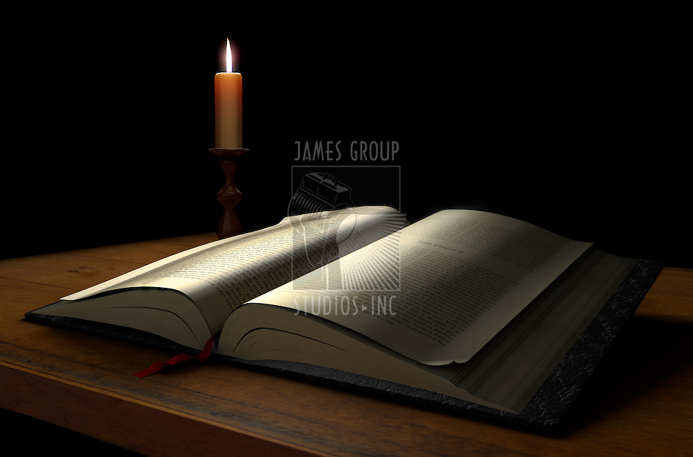 An open book on a dark background illuminated with a candle