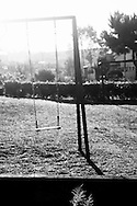 """Empty swing at a playground. Childhood must not be a period of crisis. In Portugal , as in generally the  """"occidental world"""", the public debt extends to future generations, forming a depressing future where insecurity reigns. The austerity policies affect human evolution in its most basic principles. What is the future? Children are the future, the hope for a better world depends on education in its broadest sense. Money from taxes are not invested in education or health, are used to support the debt and the banking system. In this project I focused on a fragment of a more general work about the crisis, alluding childhood and its consequences in the current socio-economic context."""