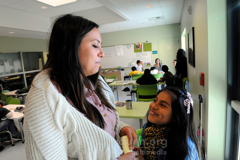 "Carissa Purnell, left, and Michelle Mora, 10, during the Cesar Chavez Library's supervised study and activities program. The program includes snacks, and is funded by a ""Building Healthy Communities"" grant organized by Carissa Purnell, manager of technology for the library."