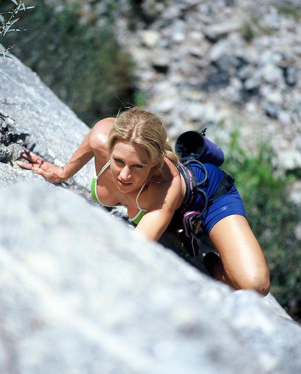 Female rock climber scales rock face in Big Bear, CA