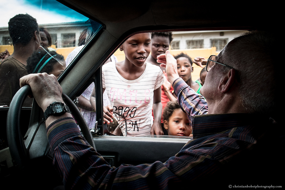 (2013) Father Hermann arrives at Damara 6, a district in Katutura township. The people gather very quick around the car when he arrives, they say they recognize the sound of the engine of his car even before they see it.