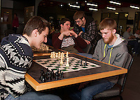 Laconia High School students Nemanja Boskivic and Johnny Spencer stragegize their moves while Bryden Wright and Curtis Gosnall look on during the City Wide Chess Tournament at Huot Technical Center on Saturday morning.  Gosnall will play the winner of this game in the final round of competition.    (Karen Bobotas/for the Laconia Daily Sun)