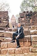 Bill Bensley in tuxedo at Angkorian temple