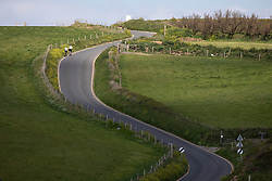 "© Licensed to London News Pictures. 11/05/2020. Newquay, UK. Cyclists ride up a steep hill on the North coast of Cornwall, the day after British Prime Minister Boris Johnson announced a 'road map' to lift lockdown restrictions due to Covid-19, (Coronavirus). A rise in ""staycations"" - the concept of holidaying in your home country rather than travelling abroad - is expected, with many visitors planning to visit Cornwall. However, an ongoing campaign titled ""#ComeBackLater"" is trying to persuade tourists not to visit the county until it is safe to do so. Photo credit : Tom Nicholson/LNP"