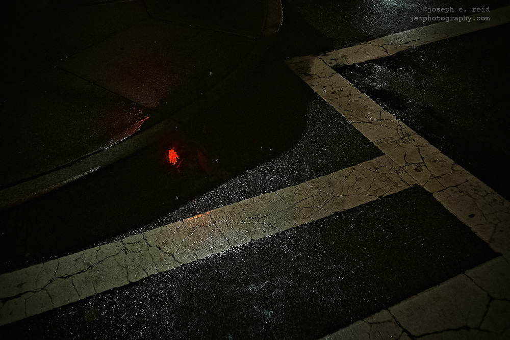 "Red ""don't walk"" symbol reflected in puddle at night"