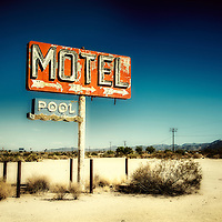 Abandoned desert motel sign on highway under a blue sky