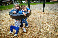 Jade Miller, 6, and Ezekiel Miller, 3, play in a tire swing as their little brother Shadrach Eberly, 2, tries to escape from underneath the swing during an outing Friday to G.O. Phippeny Park in Coeur d'Alene.